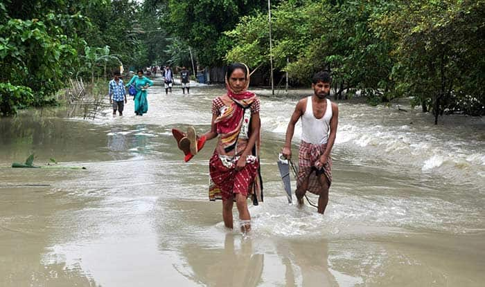 People wade through flooded Morigaon district of Assam