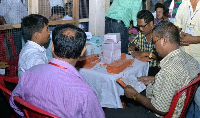 Officials counting postal ballots inside a counting room. Photo Courtesy: IANS