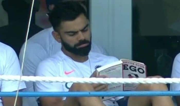 Virat Kohli, Virat Kohli gets trolled, Virat Kohli reading book during 1st Test, Kohli's book reading habit, Kohli's latest hobby, Cricket Fans troll Virat Kohli, Virat Kohli reading Detox Your Ego, Kohli draws flak for reading book, Virat Kohli's latest Dressing Room Act, Kohli's Dressing Room Habits, India vs West Indies 2019, India tour of West Indies 2019, Virat Kohli in West Indies, Cricket News