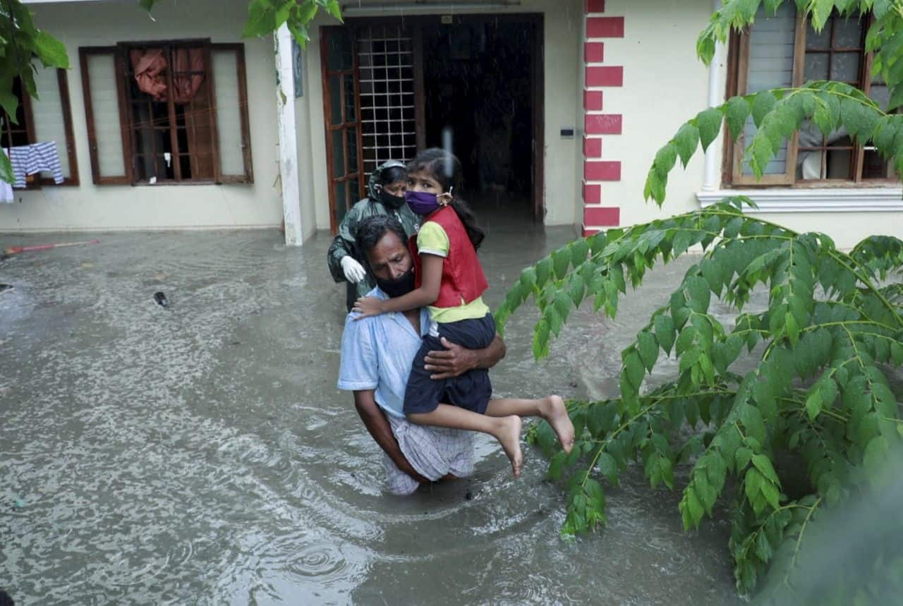 A family try to wade through their flooded house due to heavy rain in Kochi, Friday, May 14, 2021. (PTI Photo)